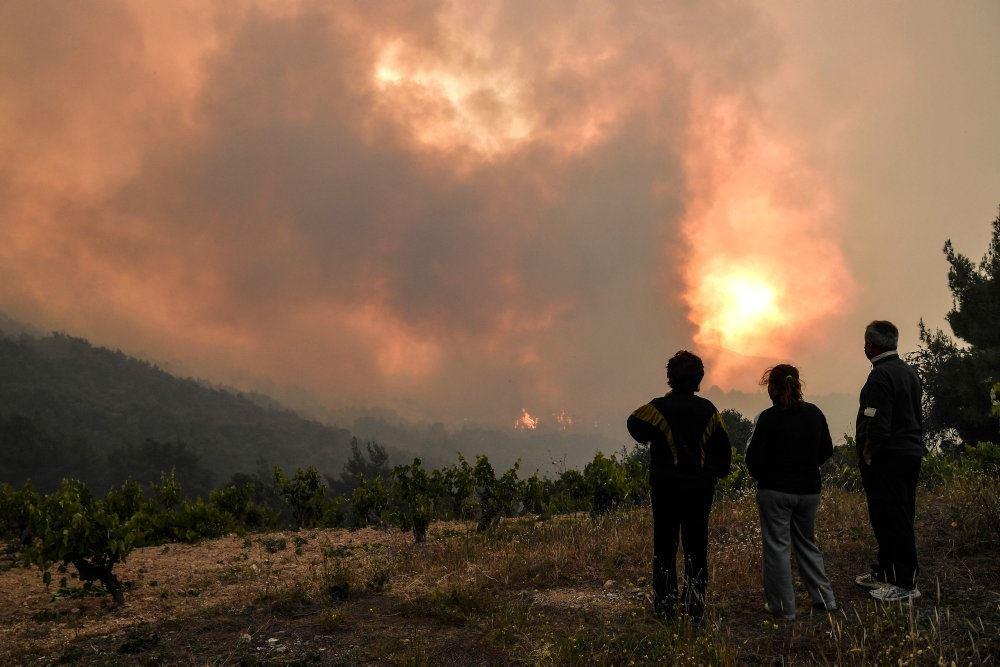 tre mennesker betragter brand