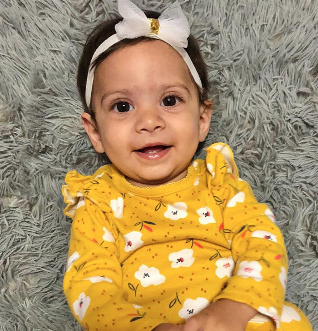 En smilende lille pige i gul kjole