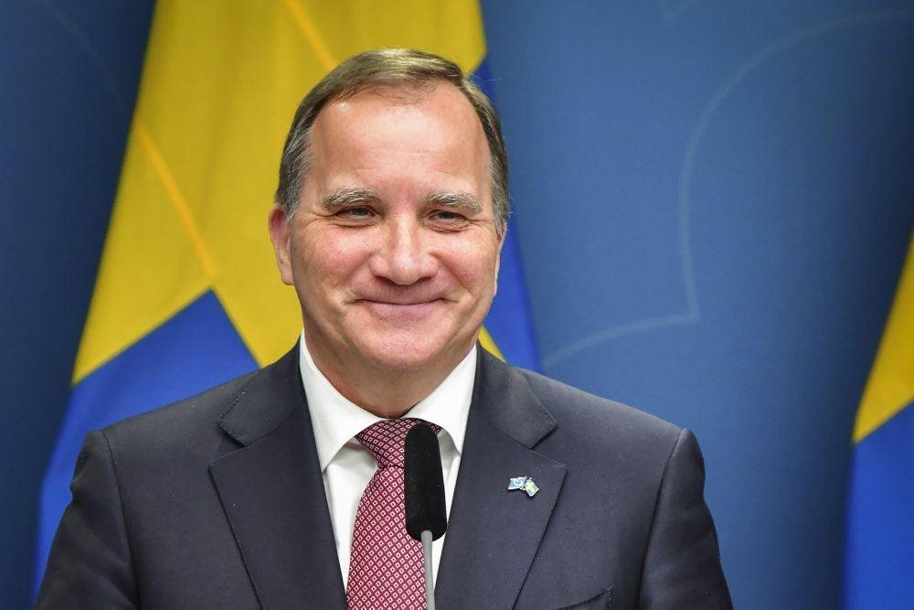 En mand i jakkesæt med et svanesk flag i baggrunden