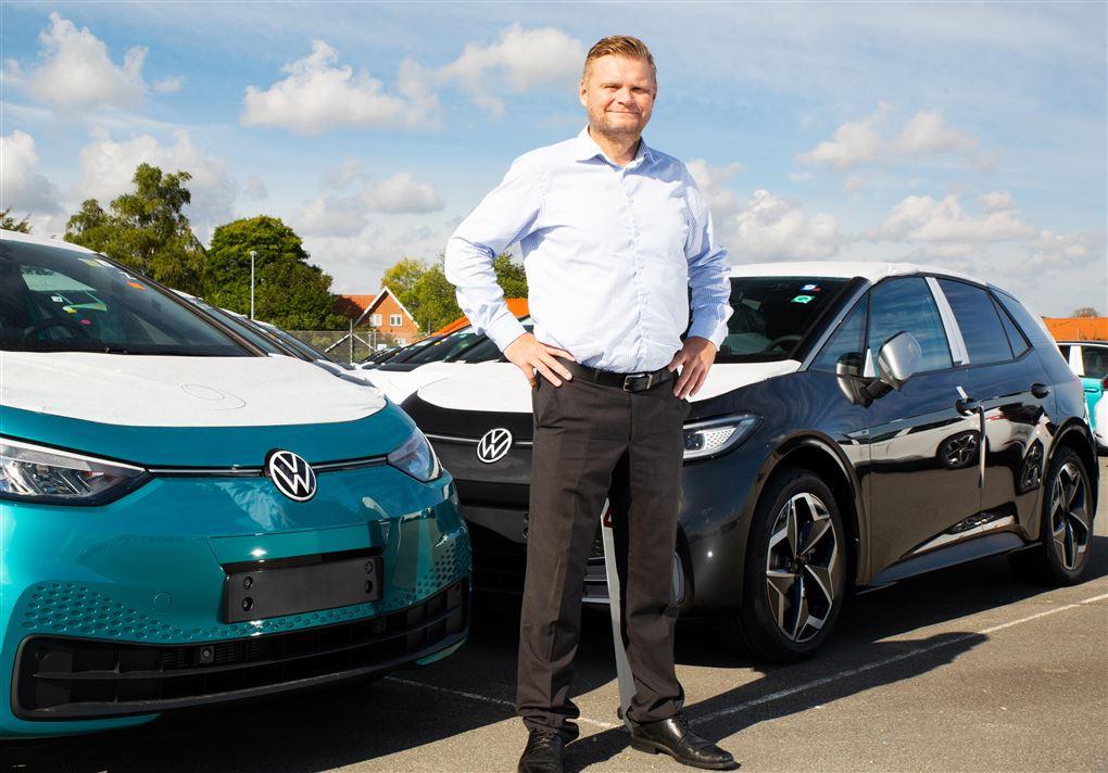 En smilende mand ved elektriske VW-biler