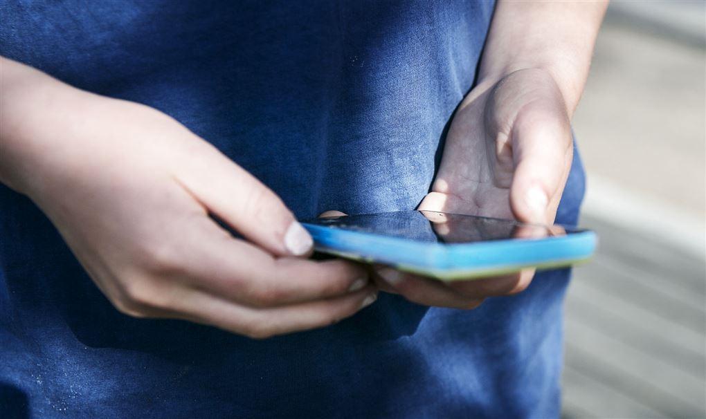 person står med en mobiltelefon