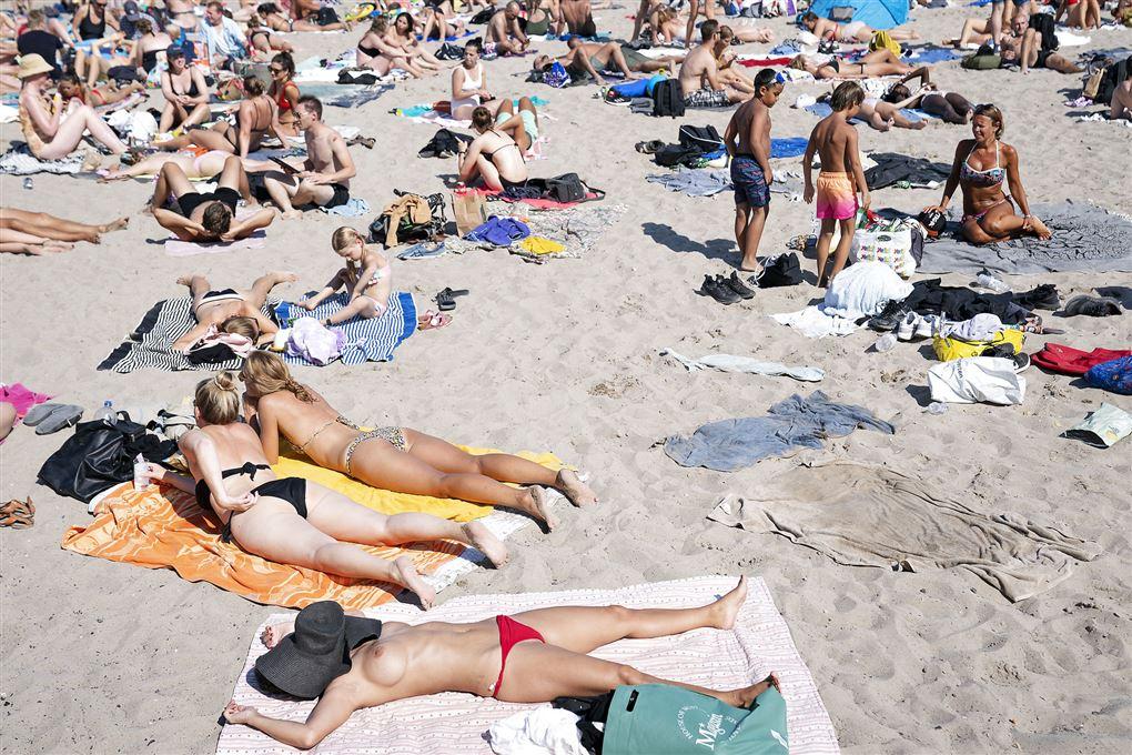 folk ligger og solbader på strand