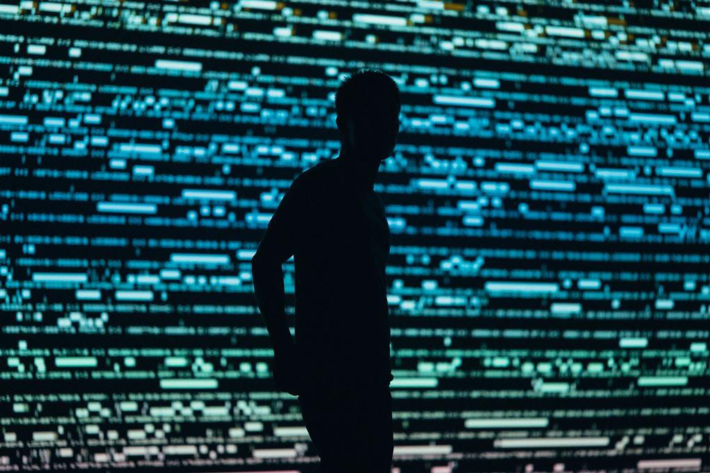 En mand står foran en kæmpe skærm med data