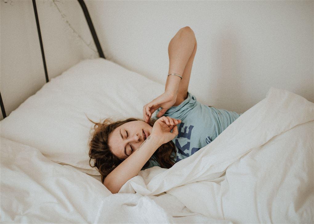 En kvinde strækker sig i sengen