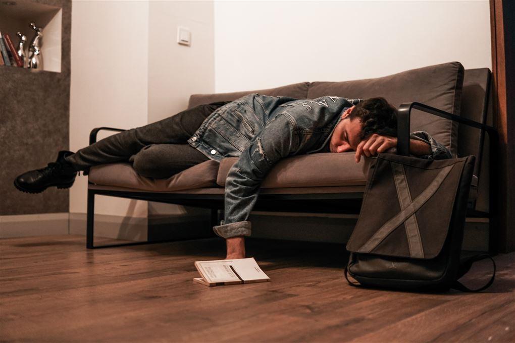 En mand sover på en briks med tøj på