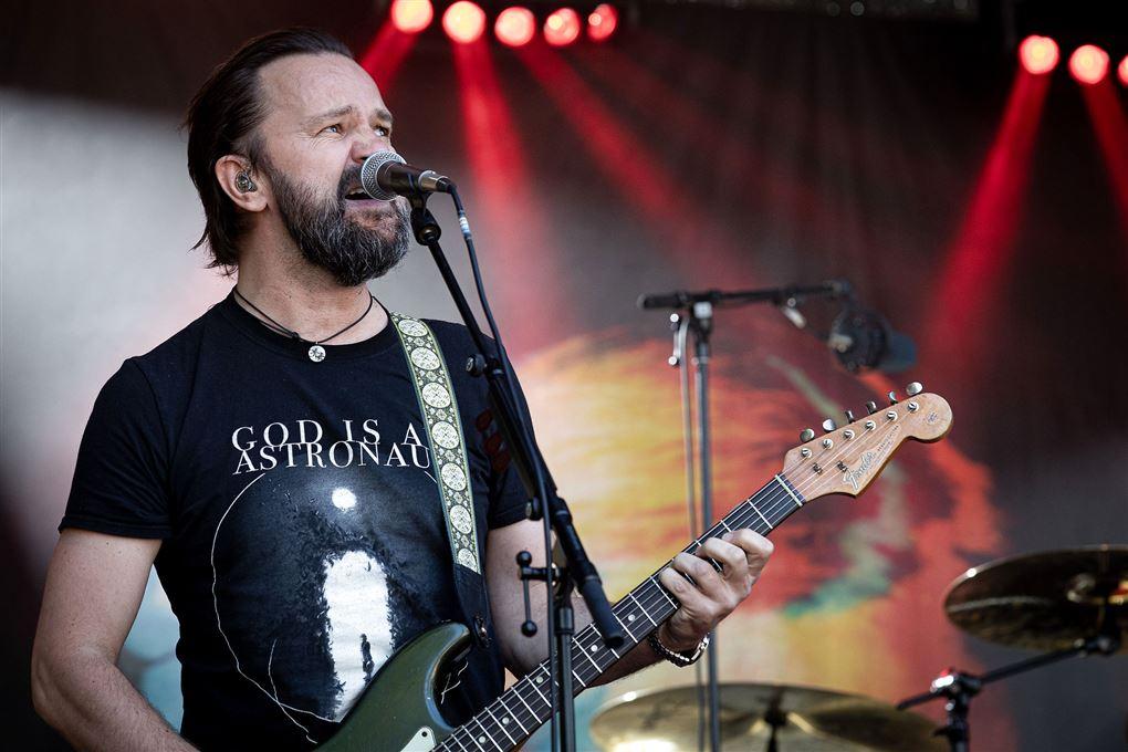 En sanger på scenen med guitar og fedtet hår