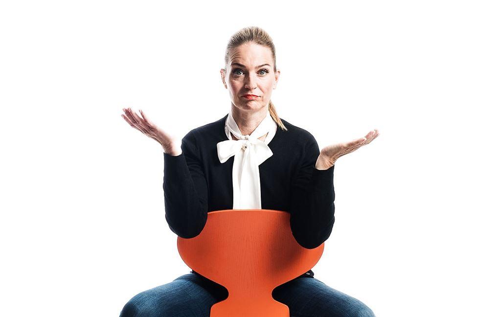 annette heick sidder på stol og slår ud med armene