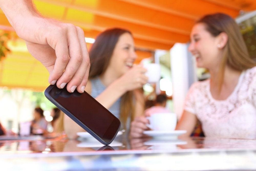 person tager mobiltelefon fra bord