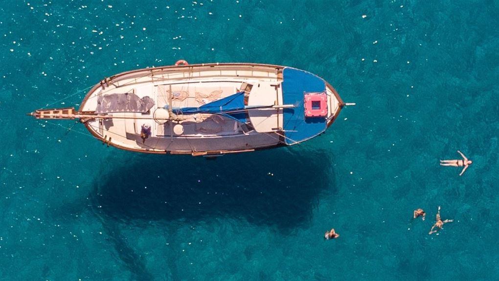 båd set ovenfra ligger på azurblår hav