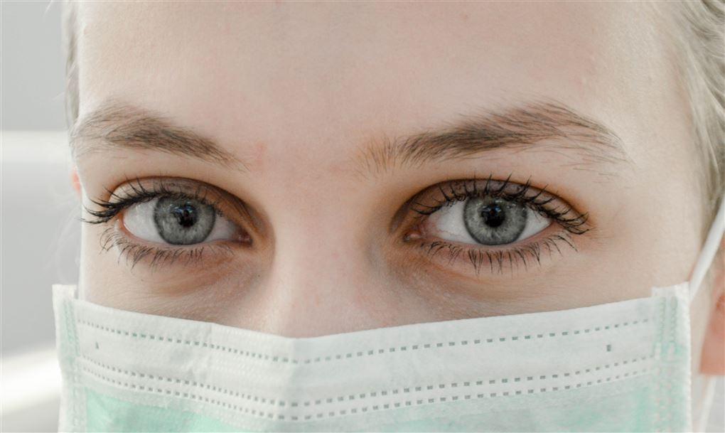 En kvinde med mundbind helt tæt på. Man kan kun se hendes øjne og det øverste af mundbindet.