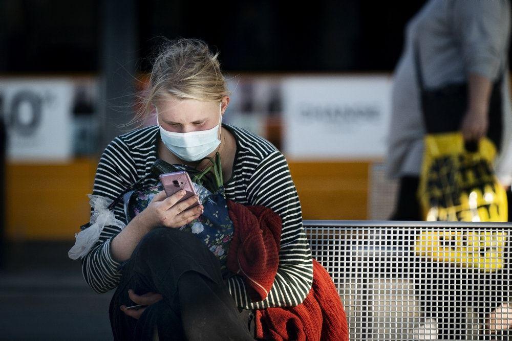 kvinde sidder med mundbind og kigger på mobiltelefon
