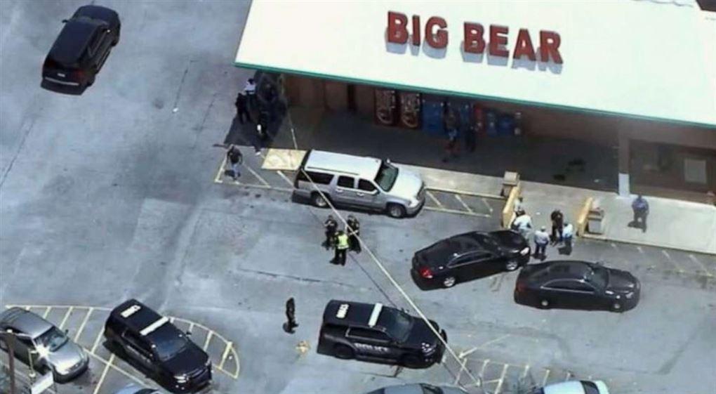 Et supermarked ovenfra med politibiler omkring det