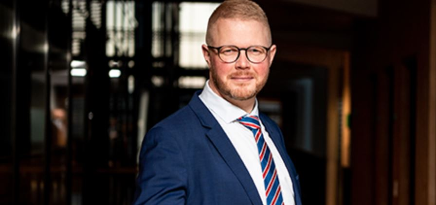 En mand i jakke og slips og briller