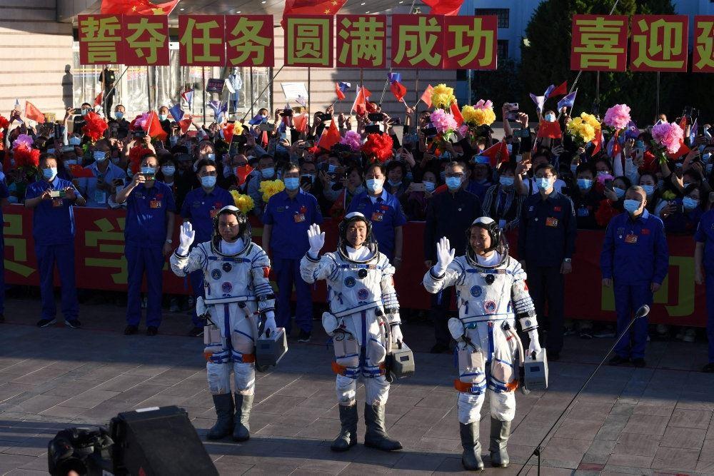 tre astronauter vinker