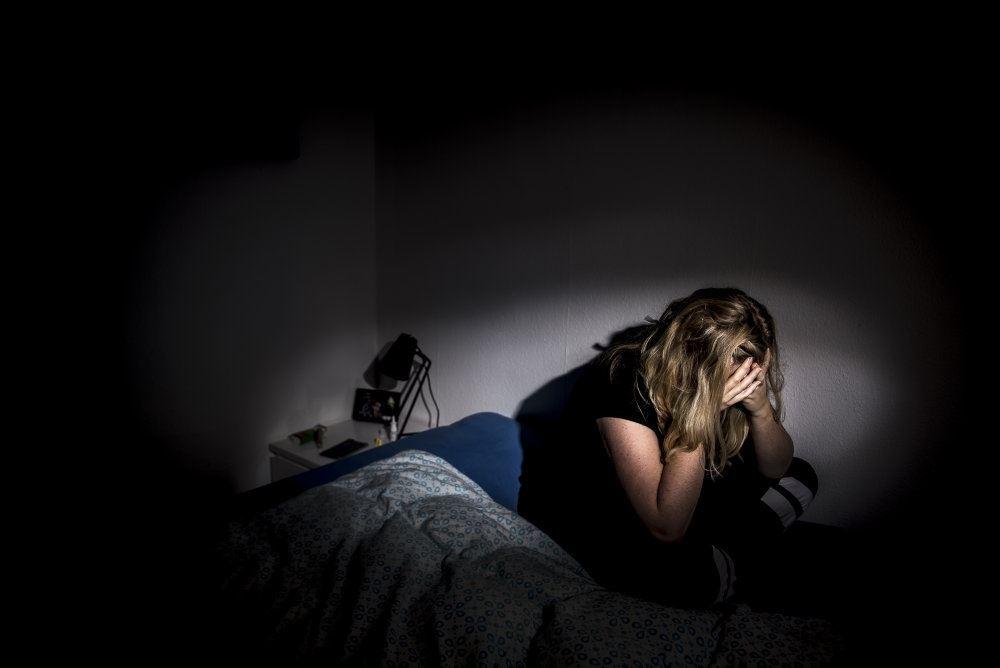 modelfoto af ulykkelig pige i seng