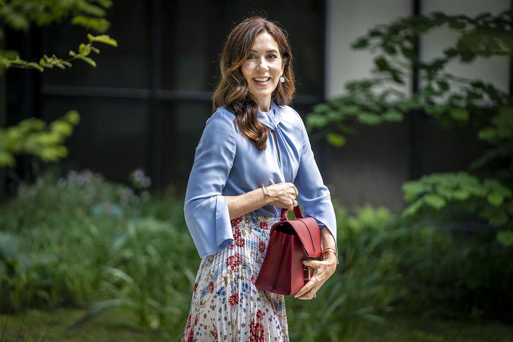 Kronprinsesse Mary står med rød taske