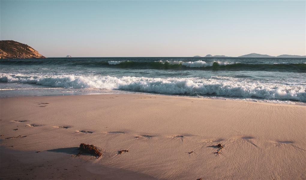 En strand med bølger og sol
