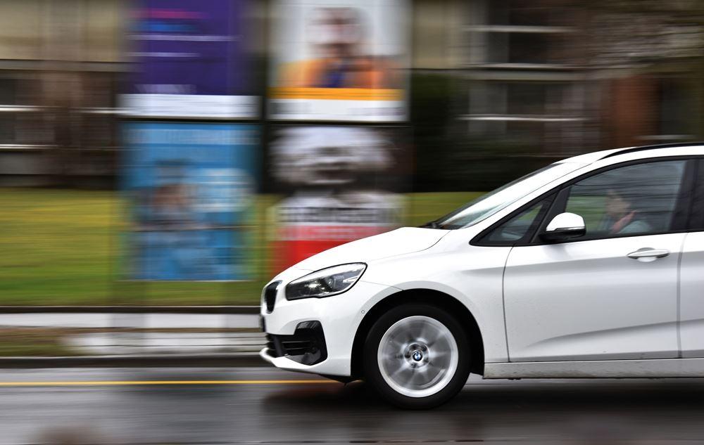 hvid bil kører på vej