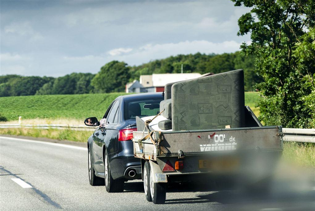 En bil med en trailer med møbler på