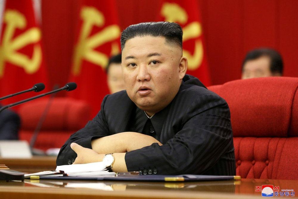 Kim Jong-un med korslagte arme i en stor rød stol. Han ser ikke specielt udmagret ud.