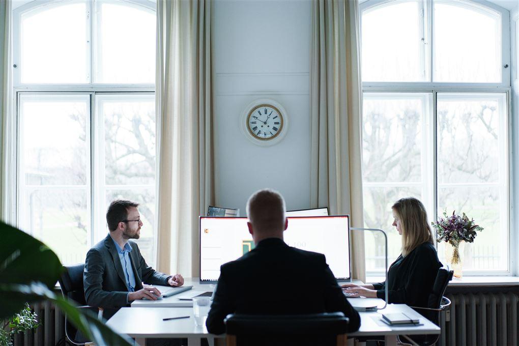 Tre mennesker ved et stort skrivebord