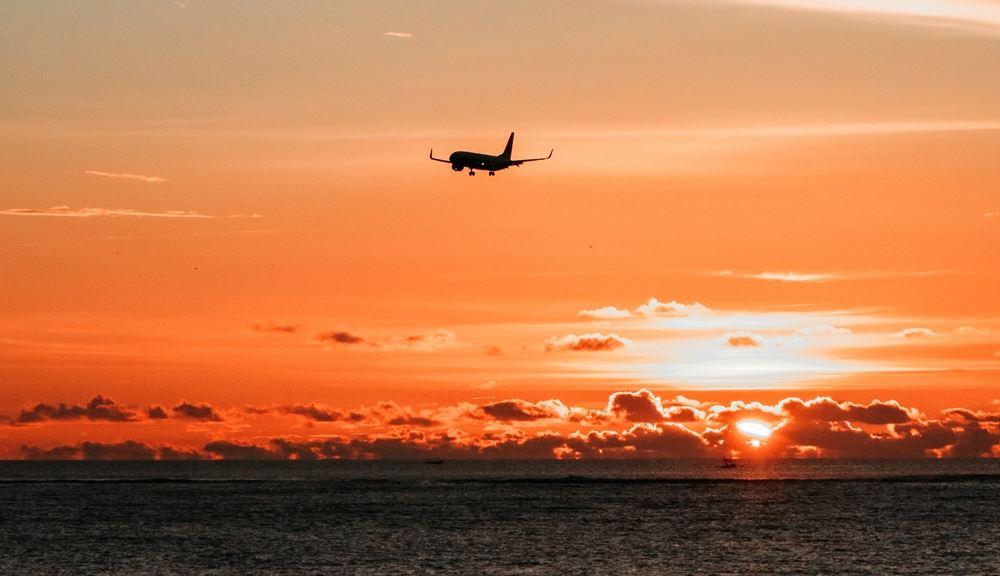 fly i luften over havet i solnedgang