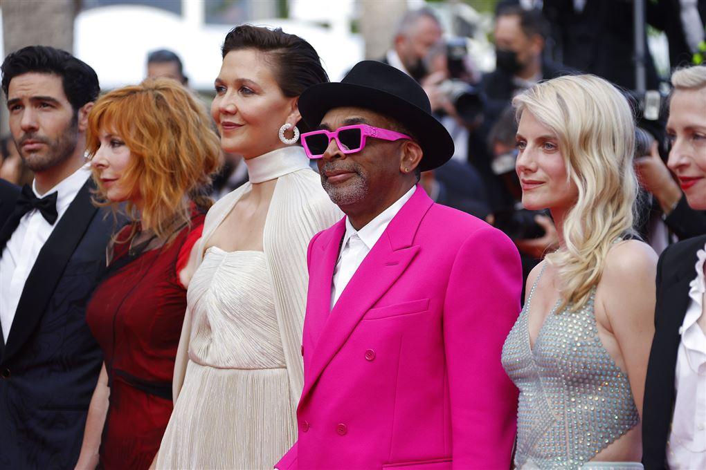 En farvet mand i pink jakkesæt på den røde løber