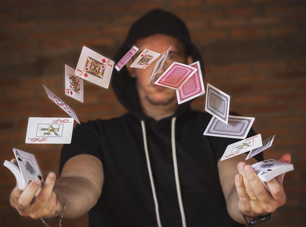 En mand i hættertrøje jonglerer med spillekort