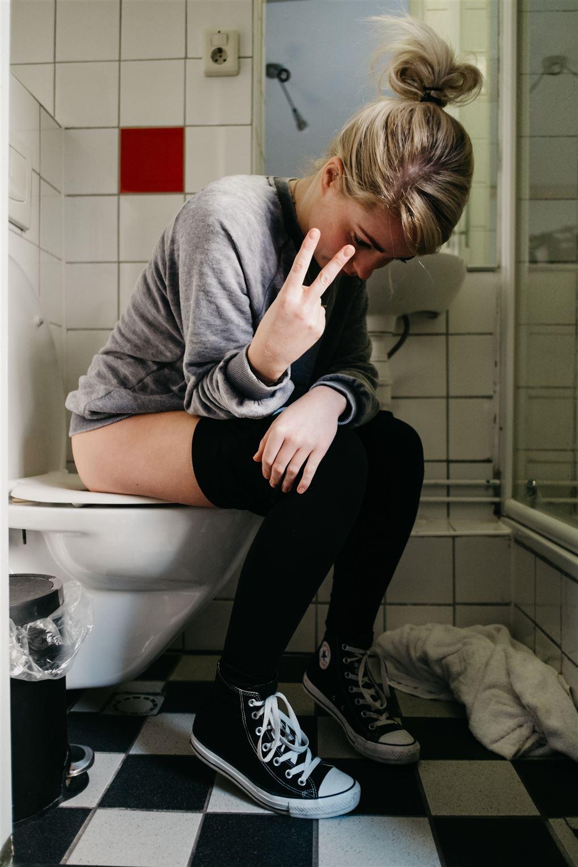 En ung kvinde sidder på toilettet