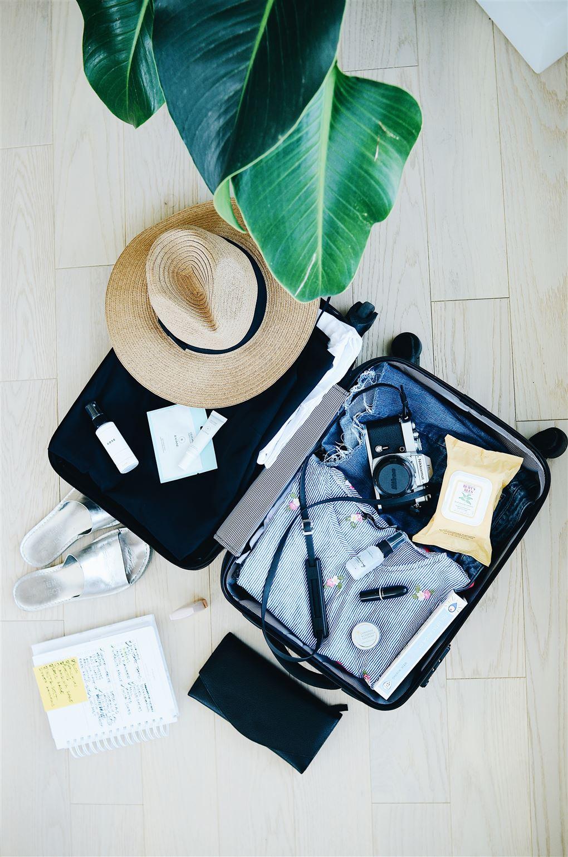 en pakket kuffert og en stråhat