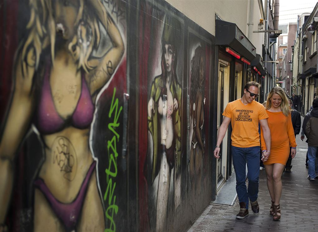 Et par går på en gade med masser af malerier af frække damer