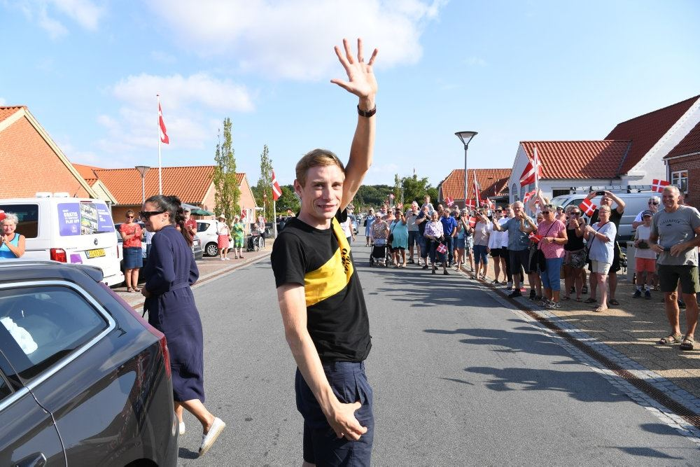 En mand vinker ved en gade