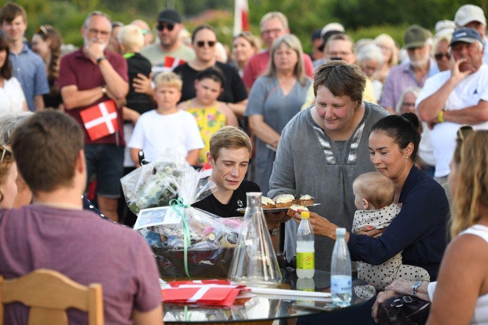 En familie sidder ved et bord med kager