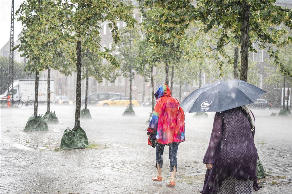 Folk går i sjoskende regn på et torv