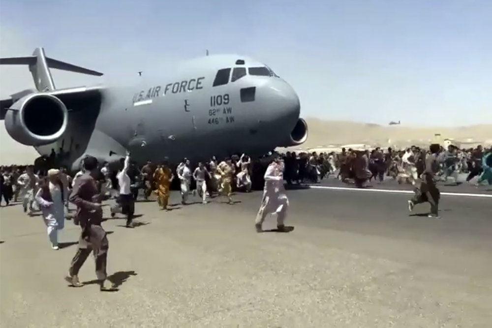 folk løber efter et militærfly i en lufthavn