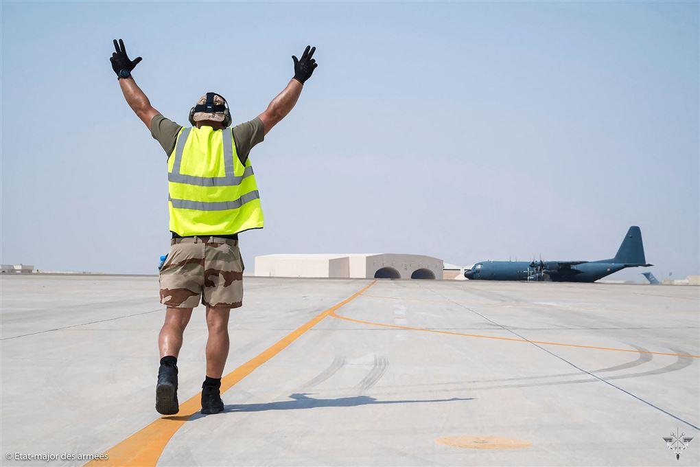 En mand i en lufthavn vinker et fly hen