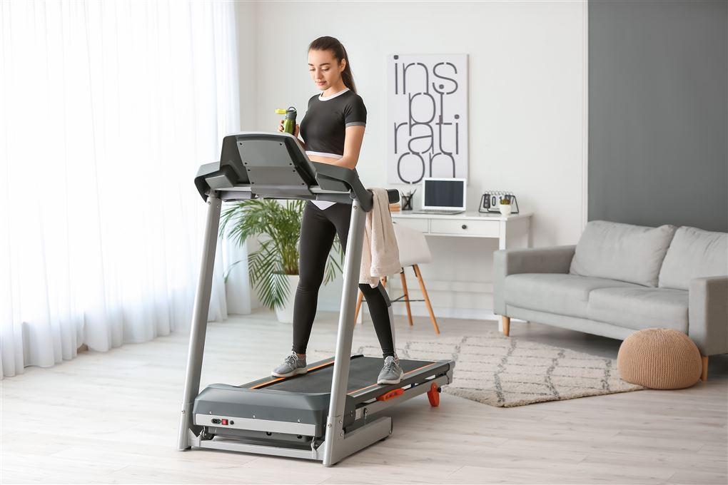 Kvinde træner hjemme på løbebånd som kan foldes sammen