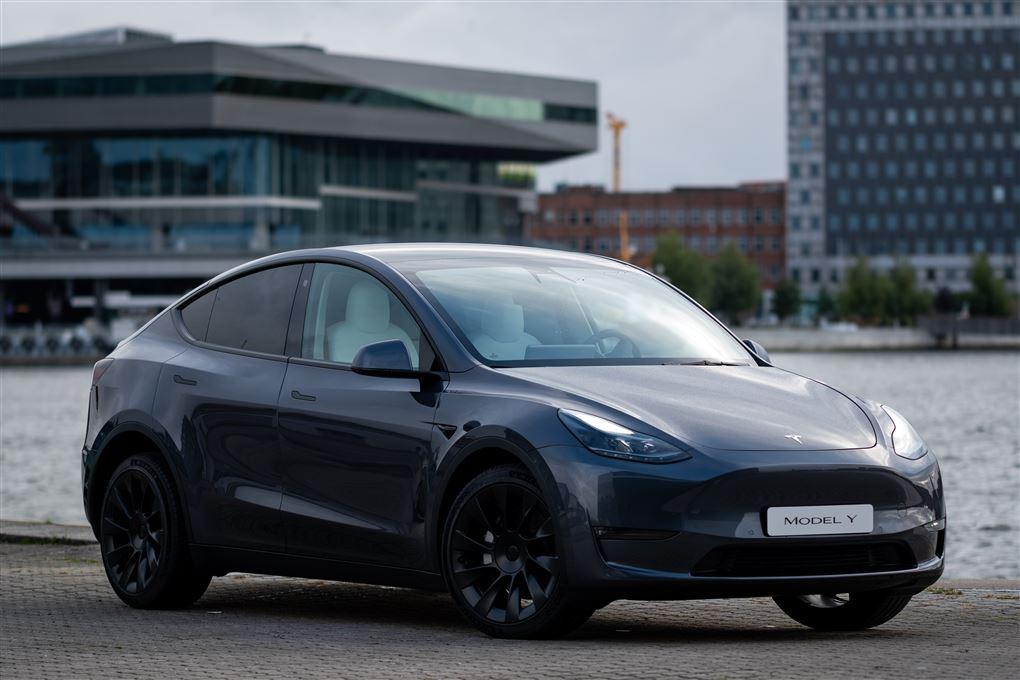 En grå Tesla ved en havnefront
