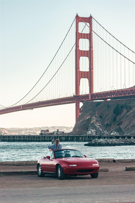 En lille sportsvogn foran en stor rød bro