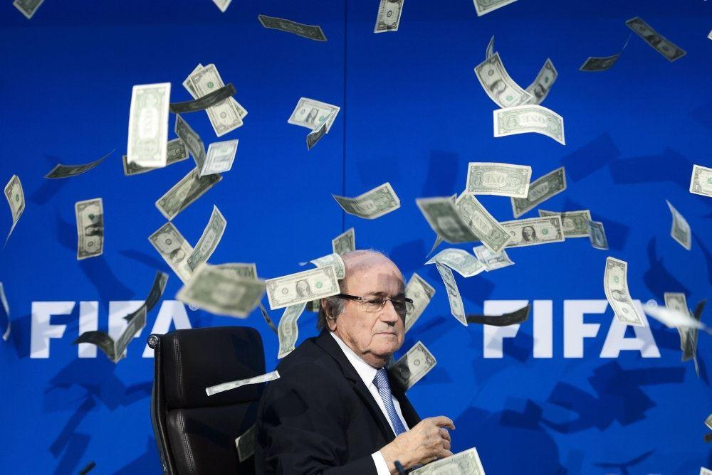 mand står på scene mens det regner med pengesedler