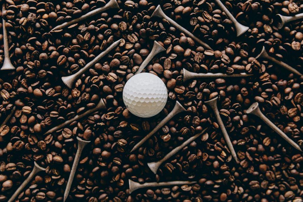 En golfbold og nogle tees i kaffebønner