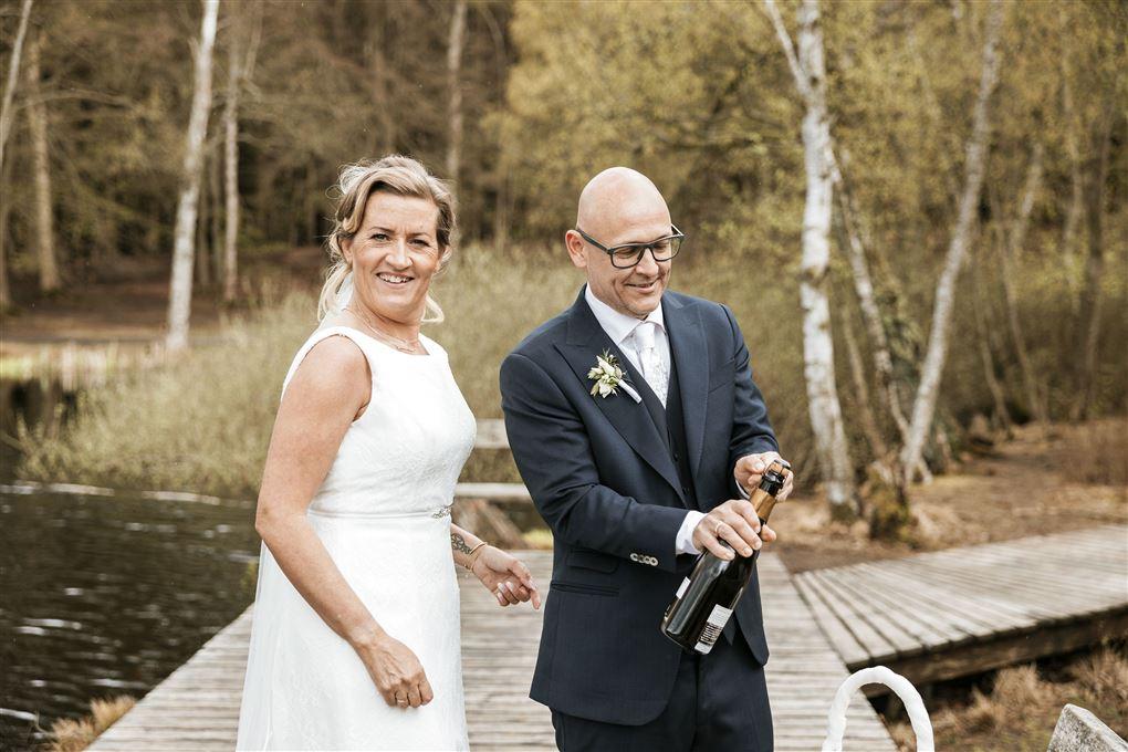 Et brudepar på en bro med champagne