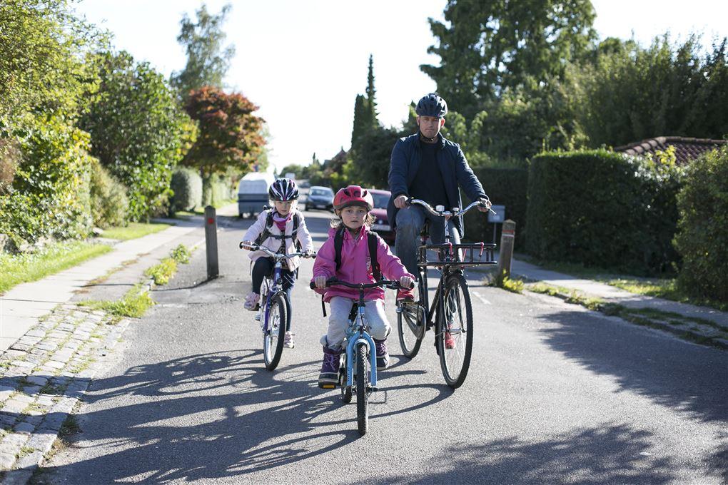 En far cykler med to små børn - alle bærer hjelm.