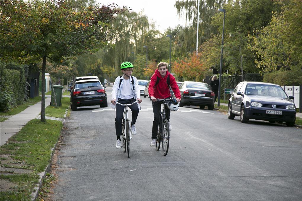 To teenagere på vejen en med hjelm en anden uden