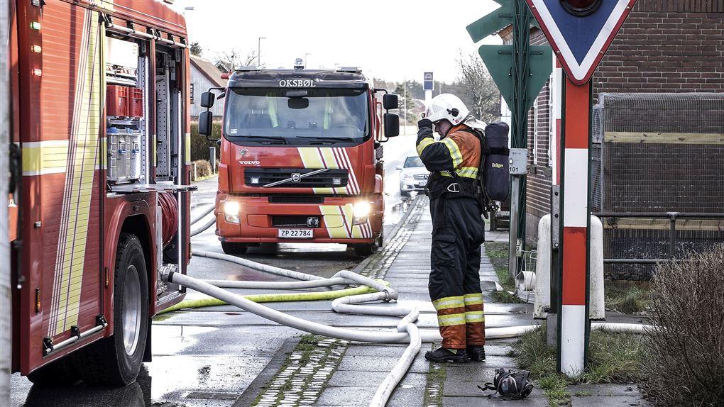 En brandmand ved to brandbiler på en gade