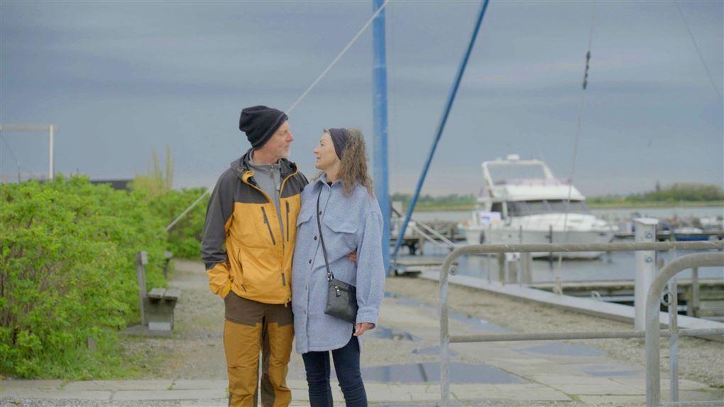 Et par i vandretøj ude ved en havn