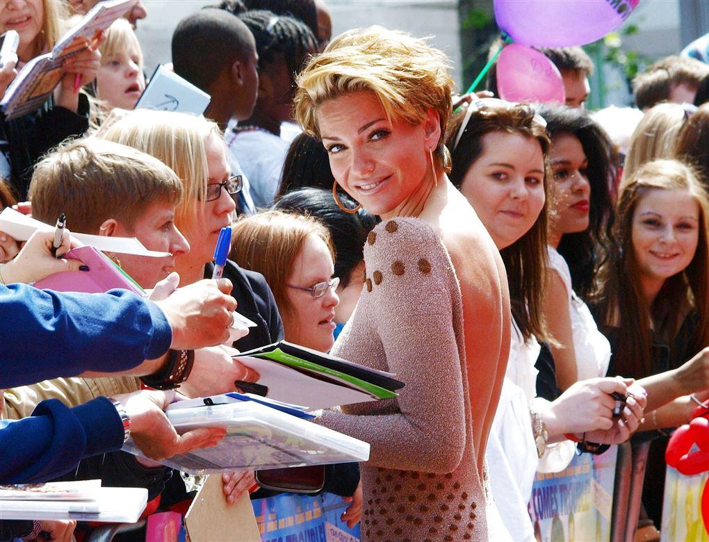 Sarah Harding giver autografer til en stor skarer af folk mens hun smiler direkte ind i kameraet.