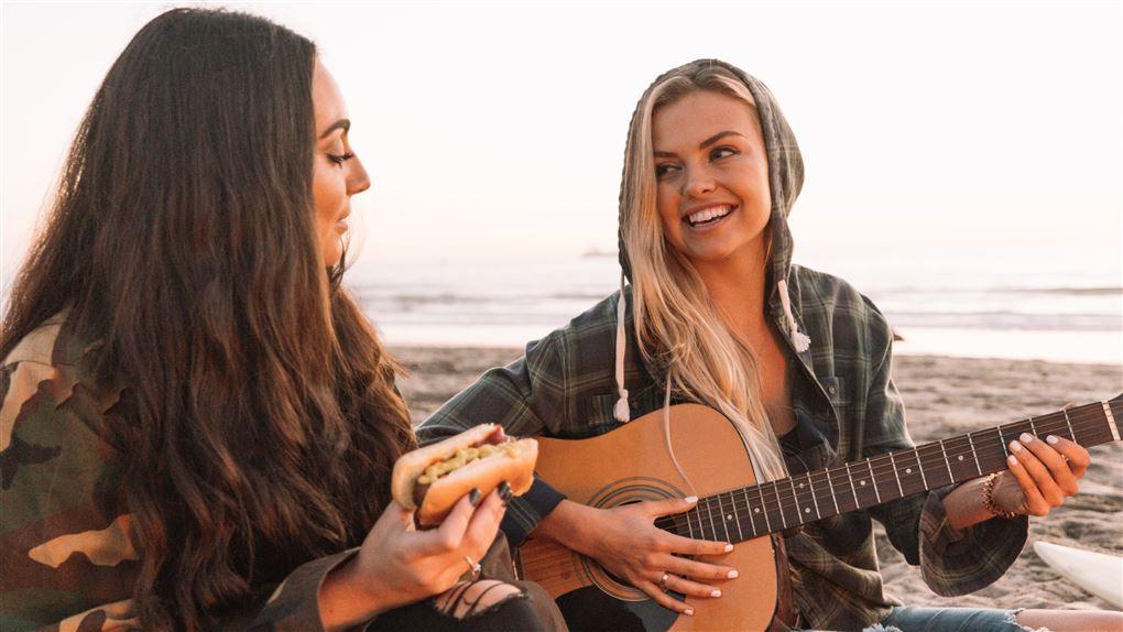 Piger på strand spiller guitar