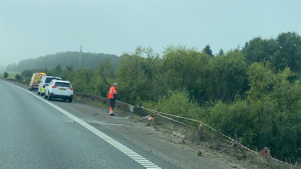 mand står ved ødelagt autoværn på motorvej