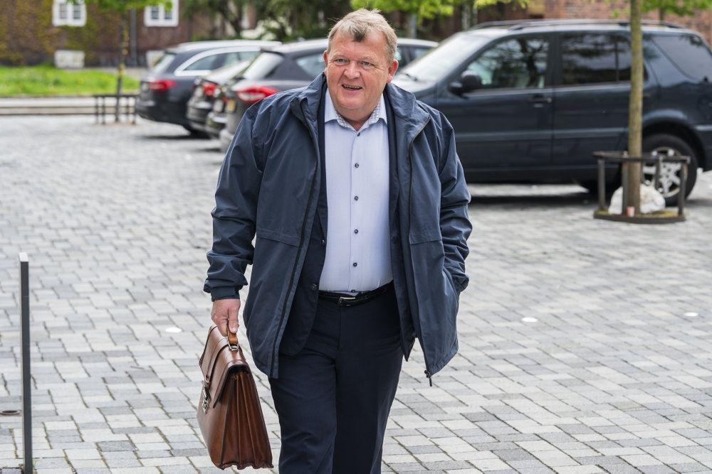 En smilende Lars Løkke Rasmussen kommer gående på en parkeringsplads med en brun læder mappe i den ene hånd.